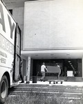 Exterior view (west entrance) of the newly completed Parker building as furniture is moved into the building, 1968
