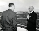 Warren Winstead, first President (1965-1969), of what was incorporated as Nova University of Advanced Technology in 1964, chats with Miami Beach Mayor Chuck Hall. The Parker building is shown in the background as it nears completion