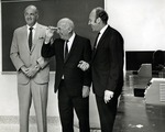 In photograph left to right: Dr. Myron Segal, surgeon and son-in-law of Abraham Mailman, Abraham Mailman ( businessman, banker, philanthropist and the founder of the town of Miramar in Florida), and Abraham Fischler (second President Nova University 1970-1992), chat with students in a classroom