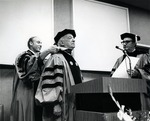 Abraham Fischler (far left), second President of Nova University (1970-1992), adjusts the gown of Abraham Mailman during a ceremony where the latter received an honorary doctorate degree