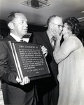 Dr. Joel Warren (left), Director Leo Goodwin Institute for Cancer Research 1969-1980, and Theresa Castro, President of the Royal Dames, presents a plaque to Leo Goodwin Sr. during a luncheon of the Royal Dames convened to honor him
