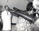 Dr. Joel Warren, Director of the Leo Goodwin Institute for Cancer Research from 1969 to 1980, looks on as Theresa Castro, President of the Royal Dames, tries out the laboratory equipment which the Royal Dames helped to purchase through their fundraising efforts