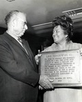 Leo Goodwin Sr. is presented with a plaque to commemorate his work as a philanthropist from the President of the Royal Dames Theresa Castro