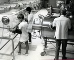 Laboratory technicians at work conducting experiments on the mono-infected or normal animals in isolators in the main laboratory of the primary genetic center of the Germ-free laboratory at the Leo Goodwin Institute for Cancer Research by Stan O'Dell