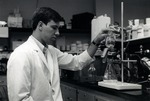 Matthew J. Orland Jr., Ph.D. student and the first recipient of the Harold Kane Kaufman Summer Scholarship awarded at what was then referred to as Nova University, conducting an experiment in the Germ-free laboratory