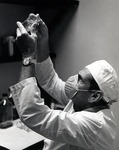 Dr. Joel Warren, Director of the Leo Goodwin Institute for Cancer Research (1969-1980), observes a specimen in the laboratory by Stan O'Dell