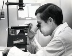 Michael Twist, Ph.D. student viewing specimens through a microscope in the Germ-free laboratory