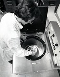 A staff member places a vial into a centrifuge in the Germ-free laboratory by Stan O'Dell