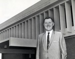 Warren Winstead, first President of what was incorporated as Nova University of Advanced Technology in 1964, stands for a photograph in front of the Edwin M. and Ester L. Rosenthal Student Center. In 1973 the Board of Trustees changed the institution name to Nova University. In 1994, Nova University merged with Southeastern University of the Health Sciences to form Nova Southeastern University